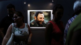 "People look at a picture of Cuba's former President Fidel Castro during the opening of the exhibition ""Fidel""."