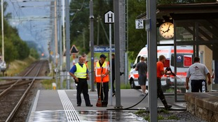 Workers clean up a platform after a suspect launched an attack in St Gallen.