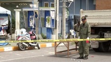 A Police Explosive Ordnance Disposal official inspects the site of a bomb blast.