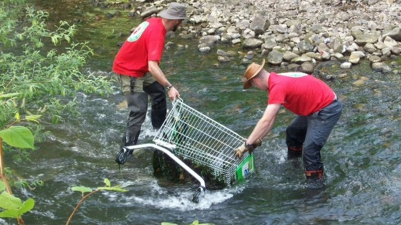 Workers clearing trolleys from river