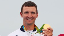 Great Britain's Giles Scott celebrates with his gold medal won in the Men's Finn on the eleventh day of the Rio Olympic Games, Brazil.