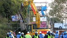 A mechanical vehicle begins to demolish the scaffolding tower at the main entrance to the Dale Farm travellers site near Basildon, Essex.