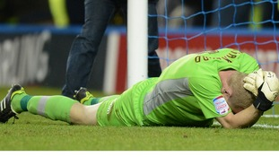 Sheffield Wednesday goalkeeper Chris Kirkland clutches his face after being shoved.