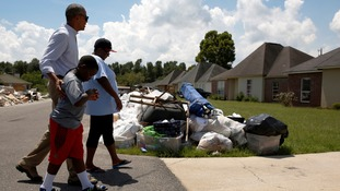 President Barack Obama surveys the damage with one family in the neighbourhood of Zachary.