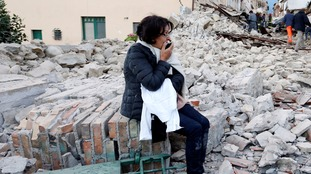 A woman sits amongst the rubble.