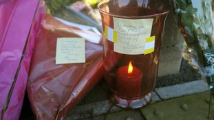Floral tributes, candles and handwritten messages left outside the Fire Station in Ely, Cardiff.