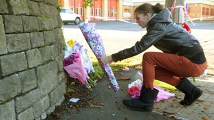 A woman places a tribute outside the Fire Station in Ely, Cardiff, where a 32-year-old woman was killed in a multiple hit-and-run incident.
