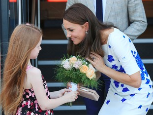 The Duchess of Cambridge is presented with a posy of flowers as she leaves Bute Mills in Luton