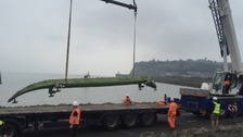 The enormous crocodile being craned onto the barrage.