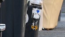 A bomb squad robot examines the item.