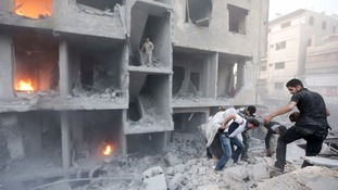 Men search for survivors at a site hit by what activists said was heavy shelling by Assad forces.