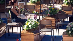 A woman sits next to a coffin to pay her respects as she attends a funeral