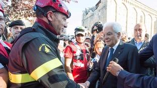 Italian President Sergio Mattarella shakes hands with a firefighter