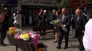 Polish ambassador Arkady Rzegocki is accompanied by MP Robert Halfon as he lays flowers.