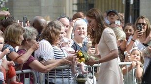 The Duchess picks up flowers from her supporters.