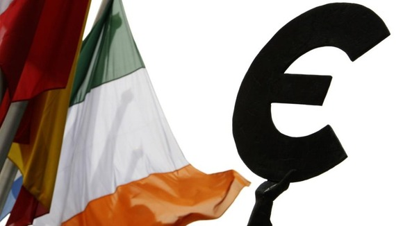 An Irish flag flies next to a symbol of the euro currency at the entrance of the European Parliament in Brussels,