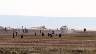 Syrian civilians as Turkish tanks roll past near the border