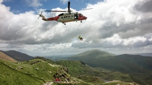 man being winched from mountain