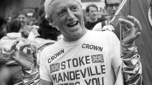 Television personality and charity fundraiser Jimmy Savile holds up a Daffodil and a medal after finishing the Marathon.