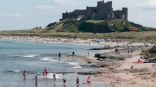 People enjoying the beach at Bamburgh.