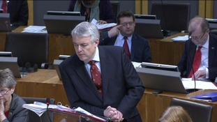 First Minister Carwyn Jones leaning on the lecturn