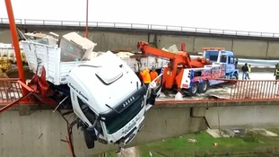 Driver survives after truck left dangling from tall bridge