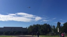 A police helicopter flies over the school after the shooting