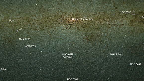 An infrared view of the Milky Way bulge that is labelled to show a selection of the many nebulae and clusters in this part of the sky.