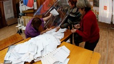 Members of local election commission empty ballot boxes to start counting vote in Russia.