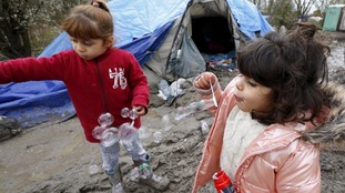Two little migrant girls play with bubbles.