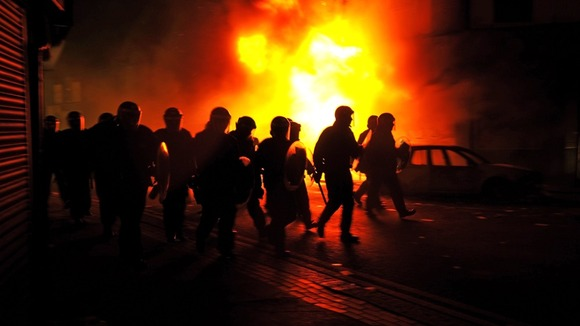 Riot police charge past burning buildings on a residential street in Croydon, south London August 8, 2011.