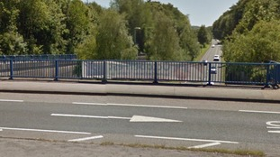 Pedestrian seriously injured after falling from bridge and onto A-Road during car crash