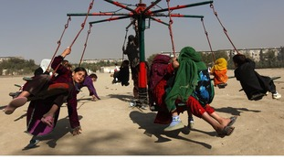 Afghan children sit on a carnival ride during Eid al-Adha in Kabul