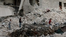 Boys make their way through the rubble of damaged buildings in Aleppo's rebel-held area of al Kalaseh.
