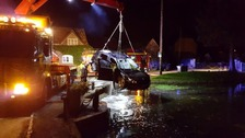 car being lifted out of the pond