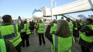 Staff take pictures as the last BMI flight lands at Heathrow Airport after arriving from Baku, Azerbaijan