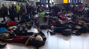 Protesters stage a 'die in' inside the airport.