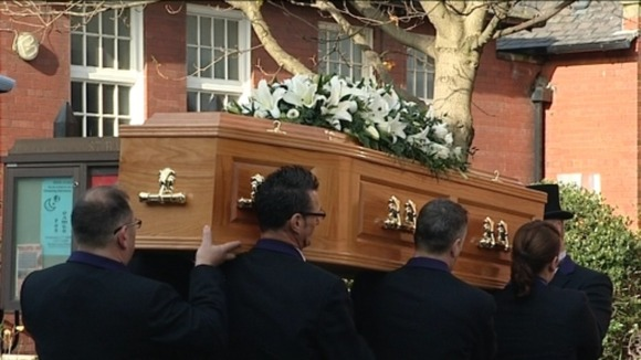 Pallbearers carry the coffin