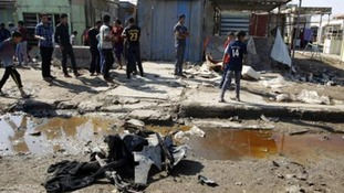 Residents inspect the aftermath of the bomb in Baghdad.