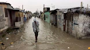 A man walks through a flooded street in Port-au-Prince.