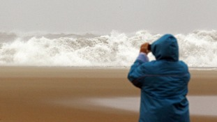 A woman photographs waves from the Atlantic Ocean in Ocean City, Maryland.