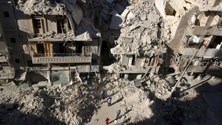 People search for survivors in the ruins after a strike on Aleppo