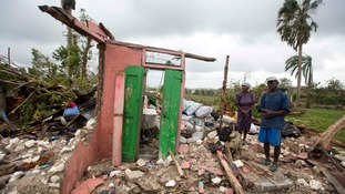 A man stands with his wife in the ruins of their home in Les Cayes, Haiti.