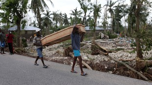 Men carry a coffin after the hurricane hit Haiti