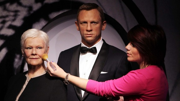 Final touches to the wax works of Daniel Craig and Judi Dench