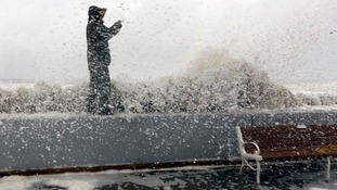 A man takes a picture while a wave crashes over the boardwalk in Ocean City