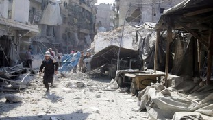 A civil defence member runs through an Aleppo market which was hit by an airstrike.