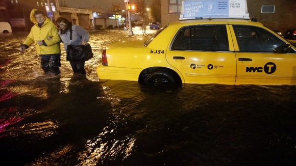 ... walk past a submerged taxi in Brooklyn, New York Photo: Reuters