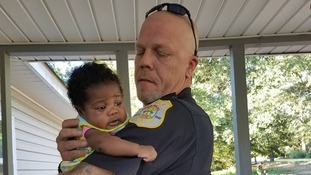 Police officer saves a baby from choking to death and parents ask him to be godfather