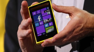 Microsoft CEO Steve Ballmer displays a Nokia Lumia 920 featuring Windows Phone 8 during an event in San Francisco